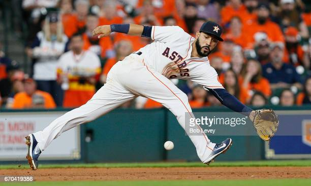 Marwin Gonzalez of the Houston Astros makes an atempt to stop a ground ball off the bat of Yunel Escobar of the Los Angeles Angels of Anaheim in the...