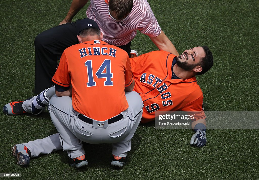 Marwin Gonzalez of the Houston Astros reacts after being hit by pitch as manager AJ Hinch and the trainer tend to him in the first inning during MLB...