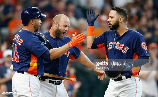 Marwin Gonzalez of the Houston Astros receives congratulations from Carlos Beltran and Evan Gattis after hitting a tworun home run in the seventh...