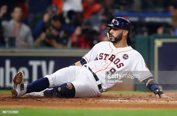 Marwin Gonzalez of the Houston Astros slides in to home plate as he scores on a sacrifice fly by Alex Bregman during the second inning against the...