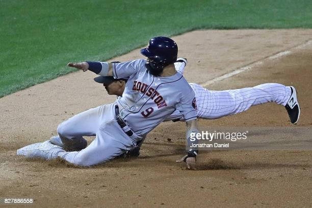 Marwin Gonzalez of the Houston Astros slides safely into third base ahead of the tag by Tyler Saladino of the Chicago White Sox in the 3rd inning at...