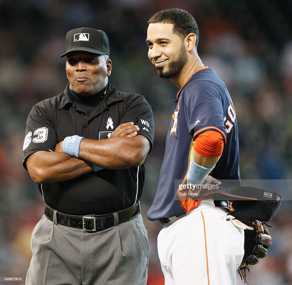 Marwin Gonzalez of the Houston Astros talks with umpire Laz Diaz during a review of a play at Minute Maid Park on June 15 2014 in Houston Texas