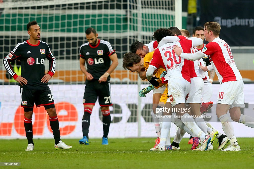 <a gi-track='captionPersonalityLinkClicked' href=/galleries/search?phrase=Marwin+Hitz&family=editorial&specificpeople=5697209 ng-click='$event.stopPropagation()'>Marwin Hitz</a>, keeper of Augsburg celebrates scoring the 2nd team goal with his team mates whilst <a gi-track='captionPersonalityLinkClicked' href=/galleries/search?phrase=Oemer+Toprak&family=editorial&specificpeople=5395932 ng-click='$event.stopPropagation()'>Oemer Toprak</a> (C) of Leverkusen looks dejected with his team mate <a gi-track='captionPersonalityLinkClicked' href=/galleries/search?phrase=Karim+Bellarabi&family=editorial&specificpeople=7158972 ng-click='$event.stopPropagation()'>Karim Bellarabi</a> (L) during the Bundesliga match between FC Augsburg and Bayer 04 Leverkusen at SGL Arena on February 21, 2015 in Augsburg, Germany.
