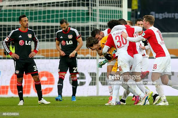 Marwin Hitz keeper of Augsburg celebrates scoring the 2nd team goal with his team mates whilst Oemer Toprak of Leverkusen looks dejected with his...