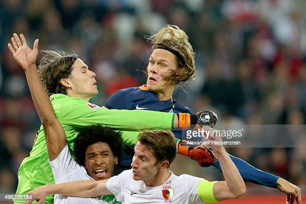 Marwin Hitz keeper of Augsburg safes the ball with his team mates Caiuby Francisco da Silva and Paul Verhaegh against Jannik Vestergaard of Bremen...