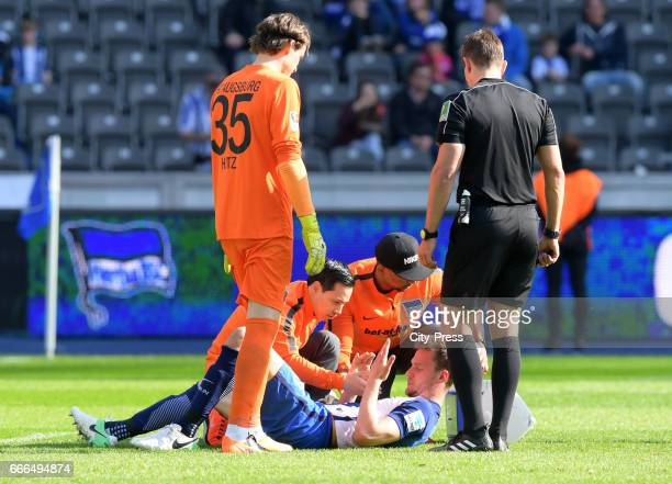 Marwin Hitz of FC Augsburg team doctor Hjun ParkSebastian Langkamp physiotherapist Frederick Syna of Hertha BSC and referee Tobias Stieler during the...
