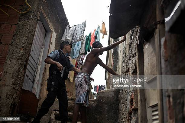 Marx a UPP officer searches a suspect for drugs and weapons in a favela of Rio de Janeiro February 17 2014