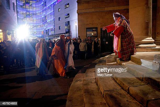 Mary and Joseph played by actors Rachel Burdon and Tim Hendy from the Winterhall Players make their way past BBC Broadcasting House and into All...