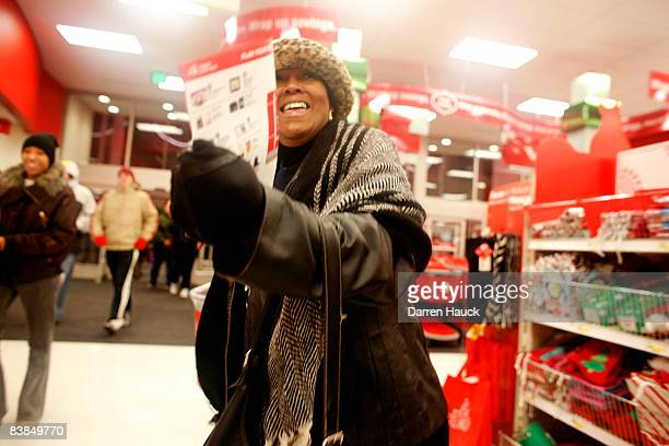 Mary Banks holds a leaflet as she and the other shoppers race inside after braving the cold temperatures out side of Target as they start the...