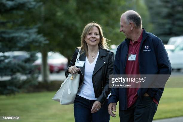 Mary Barra chief executive officer of General Motors walks with her husband Tony Barra as they arrive for the third day of the annual Allen Company...