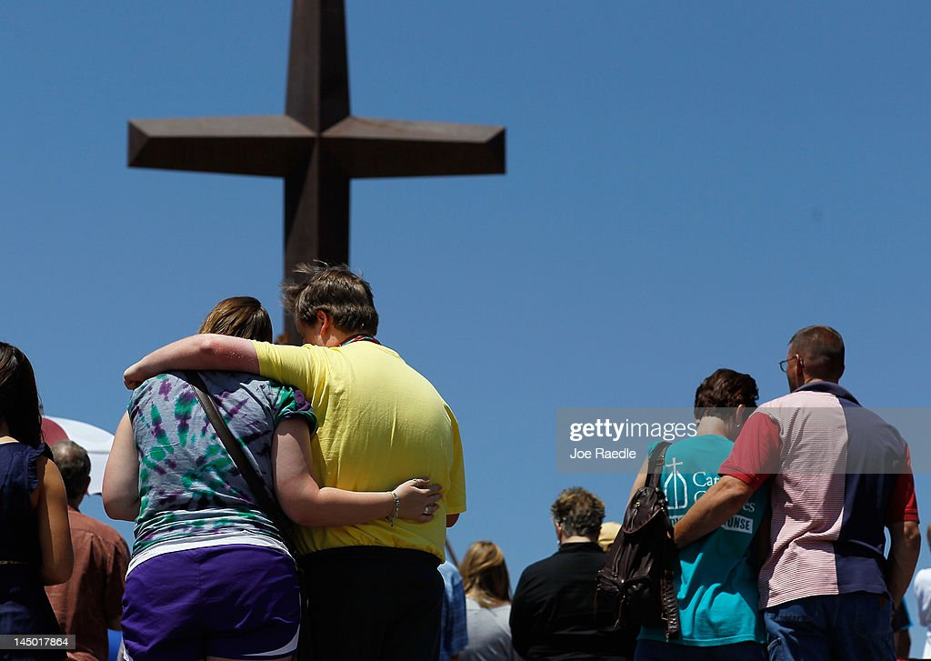 Mary Black hugs her brother Scottie Black as Dawna Middleton and Bill Cook also hug (L-R) during a prayer service in front of the iron cross that is all that remains of St. Mary's church after it was destroyed by the tornado one year ago today on May 22, 2012 in Joplin, Missouri. The EF-5 tornado devastated the leaving behind a path of destruction along with 161 deaths and hundreds of injuries, but one year later there are signs that the town is beginning to recover.