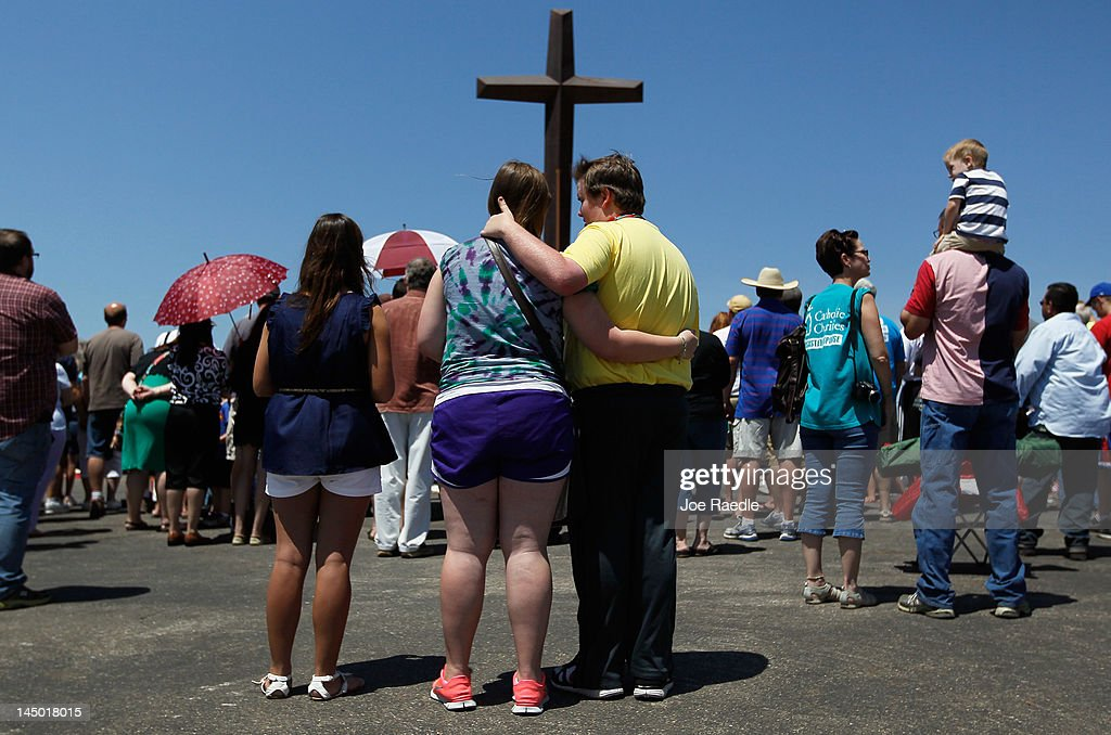 Mary Black hugs her brother Scottie Black as they and others attend a prayer service in front of the iron cross that is all that remains of St. Mary's church after it was destroyed by the tornado one year ago today on May 22, 2012 in Joplin, Missouri. The EF-5 tornado devastated the leaving behind a path of destruction along with 161 deaths and hundreds of injuries, but one year later there are signs that the town is beginning to recover.