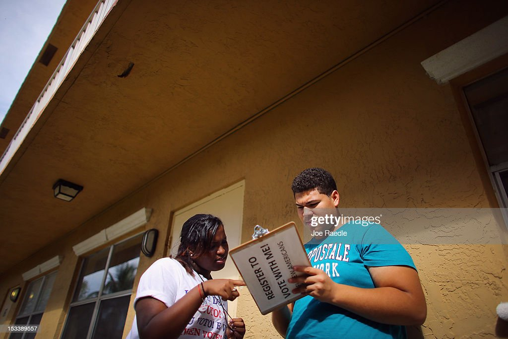 Mary Collante gets Ramon Figueroa to fill out a form as she signs him up to vote during a voter registration drive by members of the Florida...
