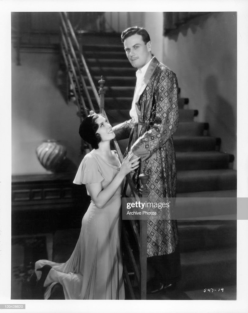 Mary Duncan kneels before Norman Foster in a scene from the film 'Men Call It Love', 1931.