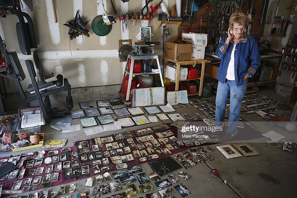 Mary Ellen Briscoe, 81, of Longmont, Colorado pauses in her garage as she looks over historic family photos trying to dry that were flooded in her basement. as residents clean up in the wake of a week of heavy flooding on September 16, 2013 in Longmont, Colorado. More than 600 people are unaccounted for and thousands were forced to evacuate after historic flooding devastated communities in Colorado.