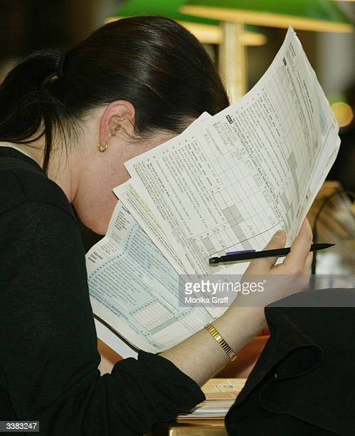 Mary Fiero holds a handful of tax forms to her face as she attempts to file her income taxes at the James A Farley Post Office April 15 2004 in New...