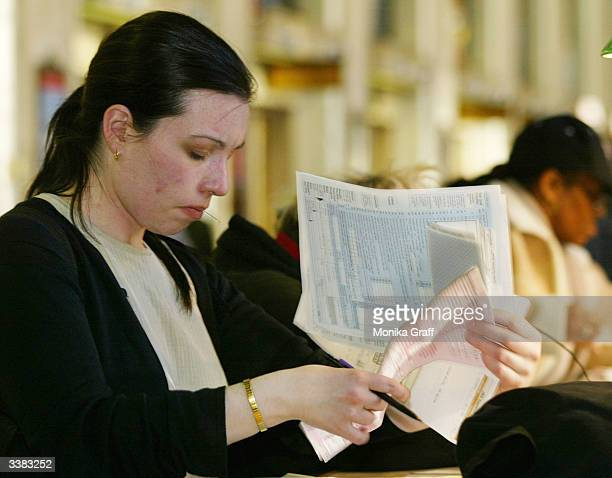 Mary Fiero shuffles through a handful of tax forms as she attempts to file her income taxes at the James A Farley Post Office April 15 2004 in New...