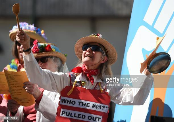 Mary Guedon of the group Raging Grannies holds up cookware while singing on stage during Tech Stands Up a rally against President Donald Trump in...