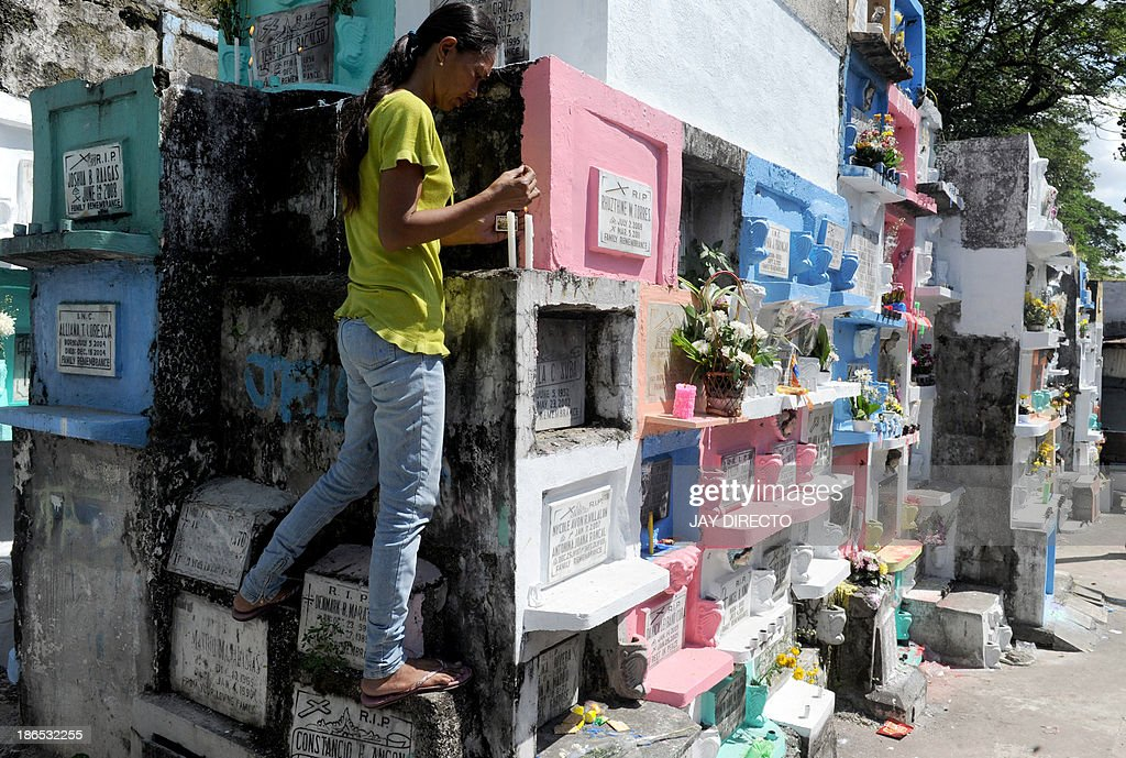 Mary Jane Mendoza (C), 34-year-old housewife light candles at the tomb of her baby, who died last year from pulmonary illness in Manila on November 1, 2013. Millions across the Catholic Philippines trooped to cemeteries to honour their dead in typically festive fashion on All Saints' Day Friday, ignoring appeals from the Church to keep the day solemn. AFP PHOTO / Jay DIRECTO
