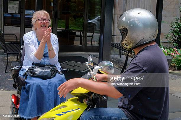 Mary Jane Owen who uses a motorized wheelchair to travel around the city and passerby Jose Ortyz exchange stories about being hit by cars on Thursday...
