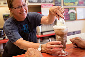 Mary Kate Reny scoops the last bit of ice cream into Herb McMahan's ice cream soda at the Waltz Soda Fountain on Main Street in Darmariscotta The...