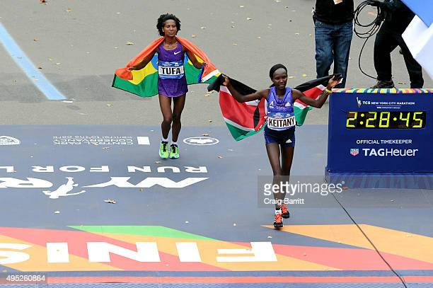 Mary Keitany of Kenya runs alongside third place Tigist Tufa of Ethiopia after the Pro Women's division at TAG Heuer Official Timekeeper and...