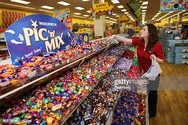 Mary Mullins a shop assistant at Woolworths straightens the Pic 'n' Mix display at a Woolworths general store in London UK Tuesday March 27 2007...