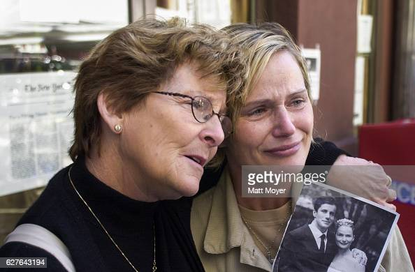 Mary Ortale left of Brooklyn NY holds a picture of herself with her missing husband Peter while she is hugged by her mother Kathi Adlum at the 69th...
