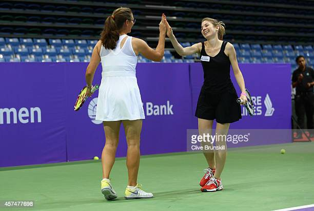 Mary Pierce of France congratulates a tennis player during a coaching clinic prior to the start of the BNP Paribas WTA Finals at Singapore Sports Hub...