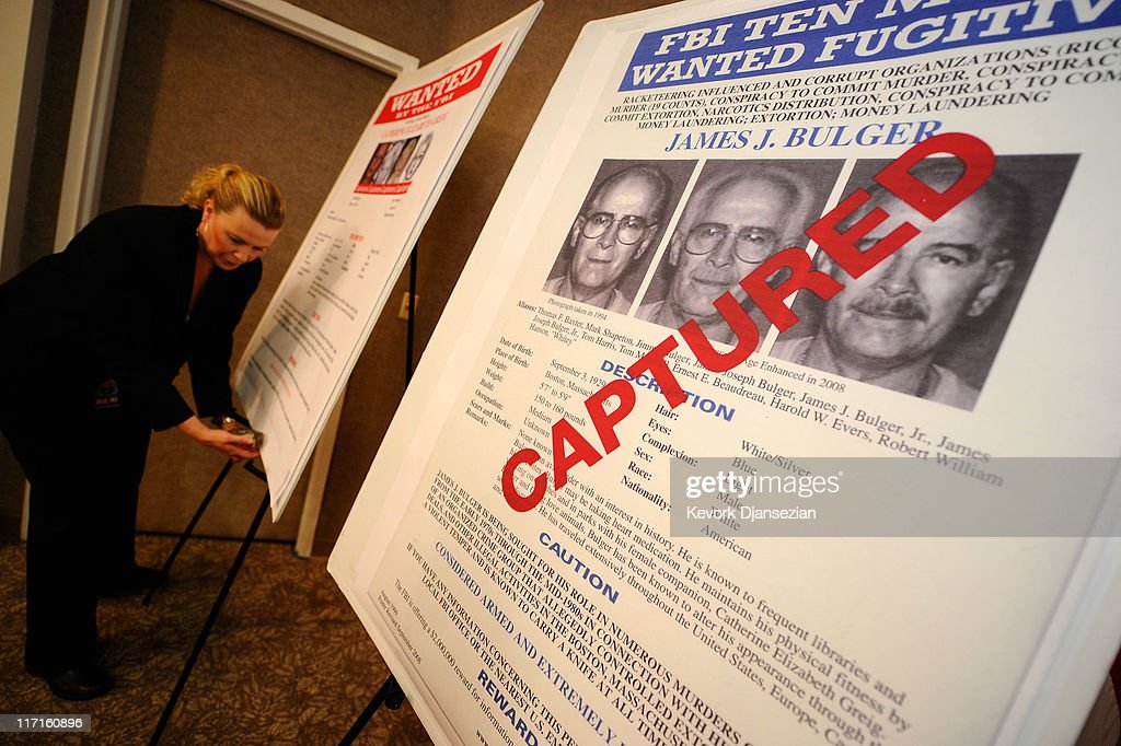 Mary Prang Special Agent wit the FBI adjusts a poster featuring fugitives Boston crime boss James 'Whitey' Bulger along with his companion Catherine...