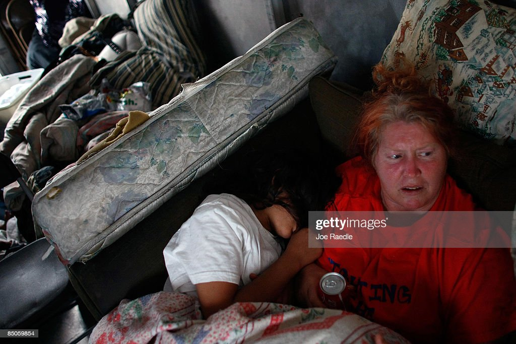 Mary Trody and her daughter, Annie Thomas, sit together in a van they parked in front of their foreclosed home that she and her family reoccupied after busting the locks and moving in with the help of the activist group 'Take Back the Land' February 24, 2009 in Miami, Florida. The family was evicted from the home and had been living in a van in the parking lot of a local supermarket since Friday when they were evicted. Mary Trody, her husband and her two children were living in the house and could not pay their bills due to what she says was predatory lending by a mortgage company. Her husband lost his job, which forced the couple and their two teenage children along with other relatives to move back in to the house before they lost it to foreclosure and now the bank owns the house.