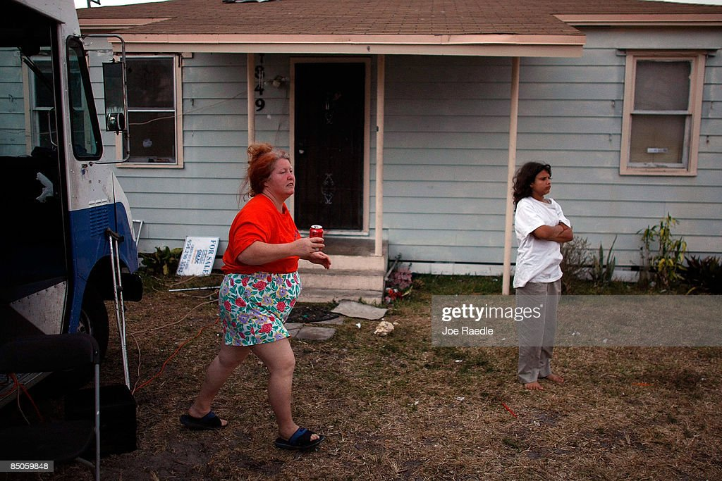 Mary Trody and her daughter, Annie Thomas, stand in front of the foreclosed home that she and her family reoccupied after busting the locks and moving in with the help of the activist group 'Take Back the Land' February 24, 2009 in Miami, Florida. The family was evicted from the home and had been living in a van in the parking lot of a local supermarket since Friday when they were evicted. Mary Trody, her husband and her two children were living in the house and could not pay their bills due to what she says was predatory lending by a mortgage company. Her husband lost his job, which forced the couple and their two teenage children along with other relatives to move back in to the house before they lost it to foreclosure and now the bank owns the house.