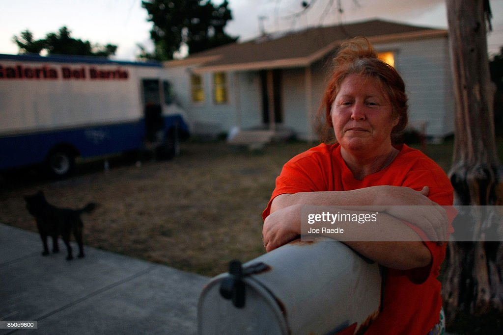Mary Trody stands in front of the foreclosed home that she and her family reoccupied after busting the locks and moving in with the help of the activist group 'Take Back the Land' February 24, 2009 in Miami, Florida. The family was evicted from the home and had been living in a van in the parking lot of a local supermarket since Friday when they were evicted. Mary Trody, her husband and her two children were living in the house and could not pay their bills due to what she says was predatory lending by a mortgage company. Her husband lost his job, which forced the couple and their two teenage children along with other relatives to move back in to the house before they lost it to foreclosure and now the bank owns the house.