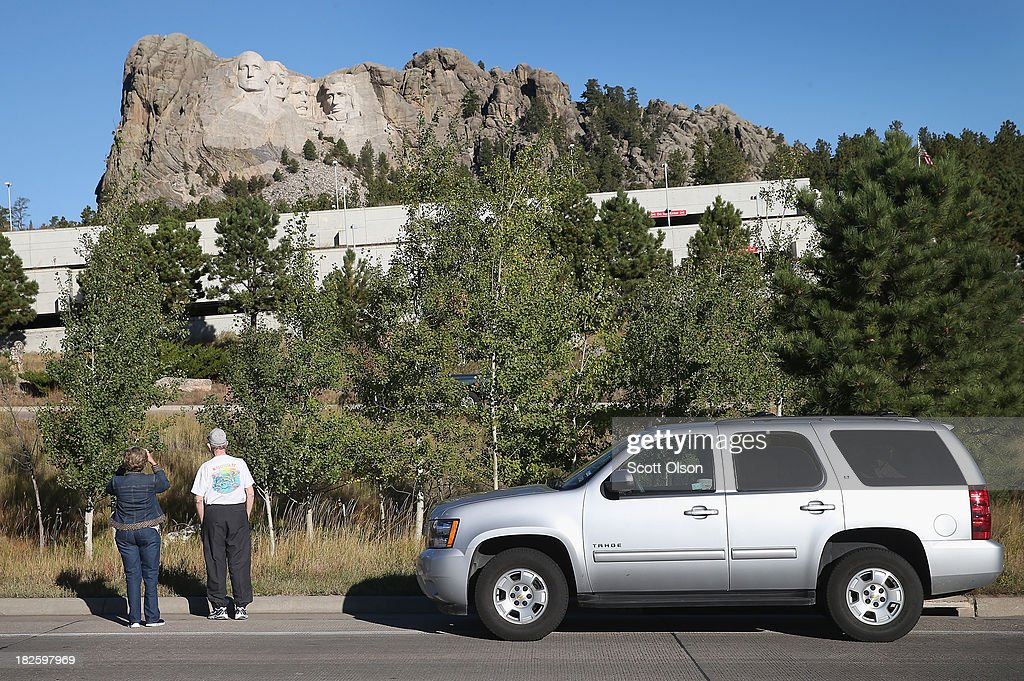 Mary William (L) and George Reininger stop to take a picture along the highway near the entrance to Mount Rushmore National Memorial on October 1, 2013 in Keystone, South Dakota. The two travelled from San Antonio, Texas to visit the memorial but, Mount Rushmore and all other national parks were closed today after congress failed to pass a temporary funding bill, forcing about 800,000 federal workers off the job. A bulletin issued by the Department of Interior states, 'Effective immediately upon a lapse in appropriations, the National Park Service will take all necessary steps to close and secure national park facilities and grounds in order to suspend all activities ...Day use visitors will be instructed to leave the park immediately...'