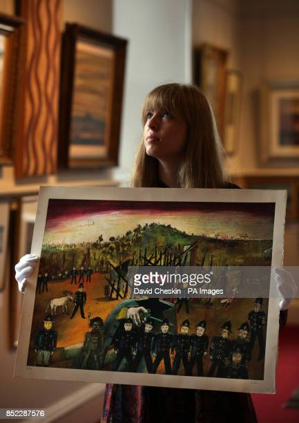 Maryan Taylor a staff member at Lyon Turnbull Edinburgh looks at a painting of folk hero Ned Kelly to be auctioned on 45 October 2013 in Edinburgh