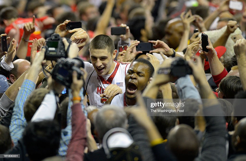 Maryland center Alex Len (25), center,left, and Maryland center Shaquille Cleare (44), center right, fight their way through a crow that mobbed the floor after the University of Maryland defeats Duke 83 - 81in NCAA mens basketball at the Comcast Center in College Park MD, February 16, 2012 .