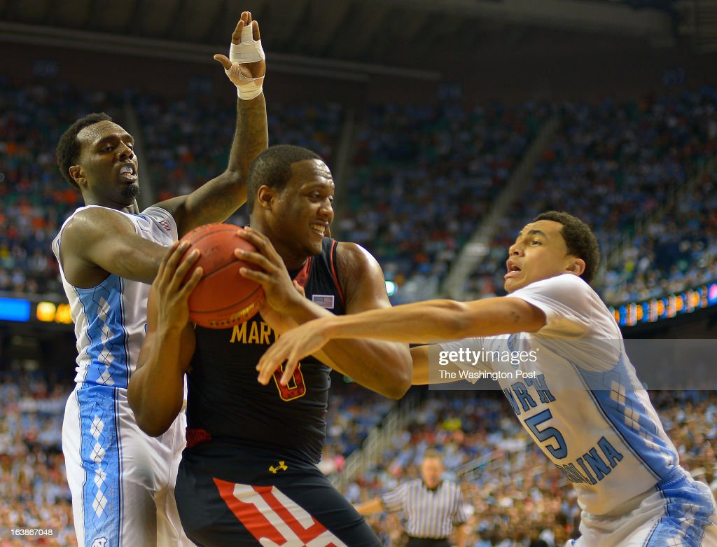 Maryland forward Charles Mitchell (0), center, is sandwiched by the defense of North Carolina guard P.J. Hairston (15), left, and North Carolina guard Marcus Paige (5) as the North Carolina Tar Heels defeat the Maryland Terrapins 79 - 76 in the ACC mens basketball semifinal at the Greensboro Coliseum in Greensboro NC, March 16, 2013.