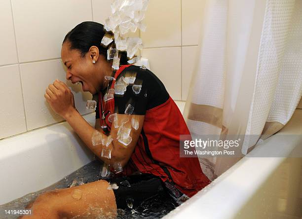 Maryland Terrapins guard Brene Moseley ducks as Kyle Tarp theDirector of Basketball Performance adds more ice to the tub during an ice bath All of...
