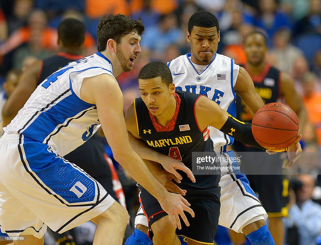Maryland Terrapins guard Seth Allen (4), center, dribbles in between Duke forward <a gi-track='captionPersonalityLinkClicked' href=/galleries/search?phrase=Ryan+Kelly+-+Jugador+de+baloncesto&family=editorial&specificpeople=15185169 ng-click='$event.stopPropagation()'>Ryan Kelly</a> (34), left, and Duke guard Quinn Cook (2) as the Duke Blue Devils play the Maryland Terrapins in the ACC mens basketball quarterfinal at the Greensboro Coliseum in Greensboro NC, March 15, 2013.