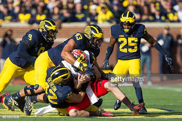 Maryland Terrapins quarterback Perry Hills is tackled by Michigan Wolverines defensive end Chris Wormley and Michigan Wolverines linebacker Ben...