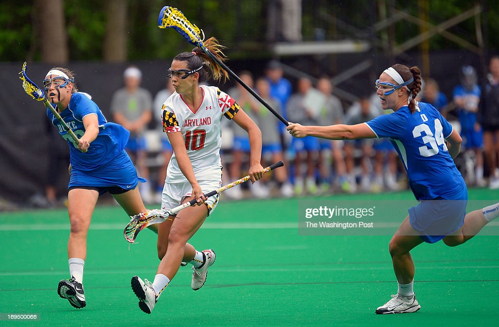 Maryland's Alex Aust, center, shoots a first half goal between the defense of Duke's Taylor Virden, left, and Mie Graham, right, during the University of Maryland defeat of Duke 14 - 9 in the NCAA women's lacrosse quarter-finals in College Park MD, May 18, 2013.