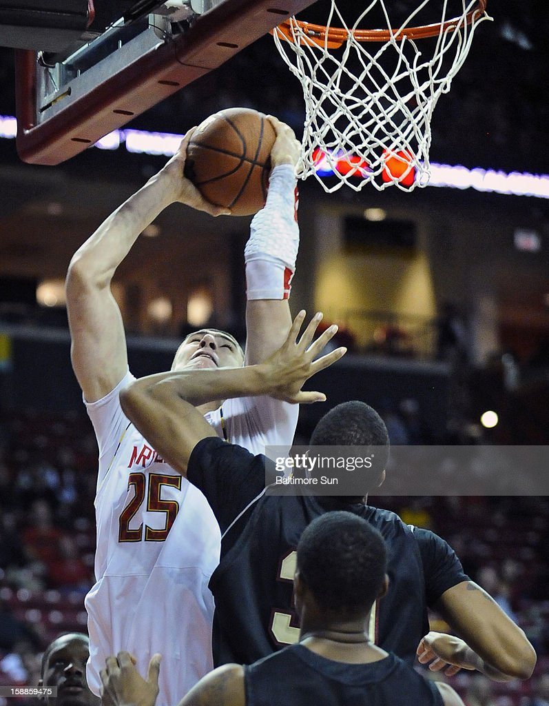Maryland's Alex Len, left, goes up for a slam-dunk over IUPUI's Donovan Gibbs in the second half of a men's college basketball game at the Comcast Center on Tuesday, January 1, 2013, in College Park, Maryland. The University of Maryland Terrapins defeated the IUPUI Jaguars, 81-63.