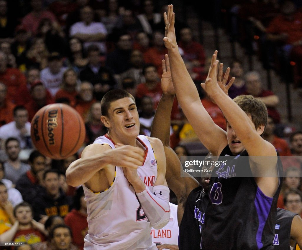 Maryland's Alex Len passes the ball under defensive pressure from Niagara's T.J. Kline during first-half action in the NIT Tournament at the Comcast Center in College Park, Maryland, Tuesday, March 19, 2013.