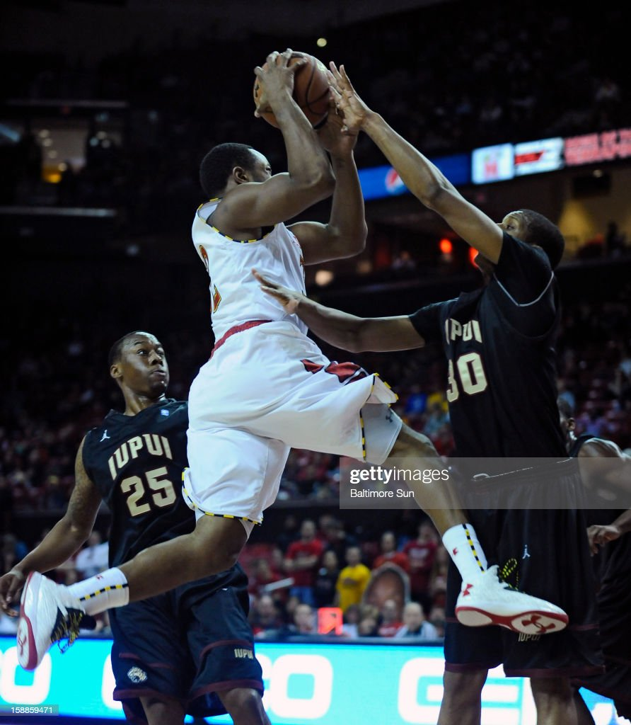 Maryland's Dez Wells, left, goes up for a basket against IUPUI's Donovan Gibbs, right, in the first half of a men's college basketball game at the Comcast Center on Tuesday, January 1, 2013, in College Park, Maryland. The University of Maryland Terrapins defeated the IUPUI Jaguars, 81-63.