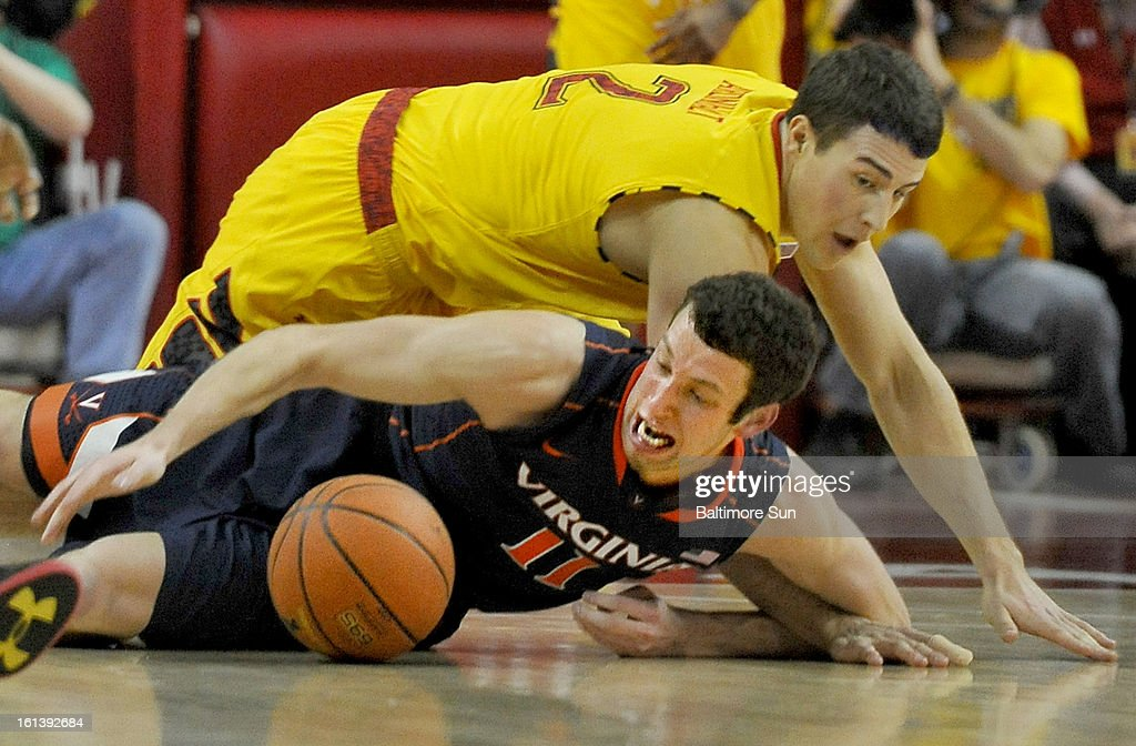 Maryland's Logan Aronhalt and Virginia's Evan Nolte dive for a loose ball during a men's college basketball game in College Park, Maryland, Sunday, February 10, 2013. Virginia won, 80-69.