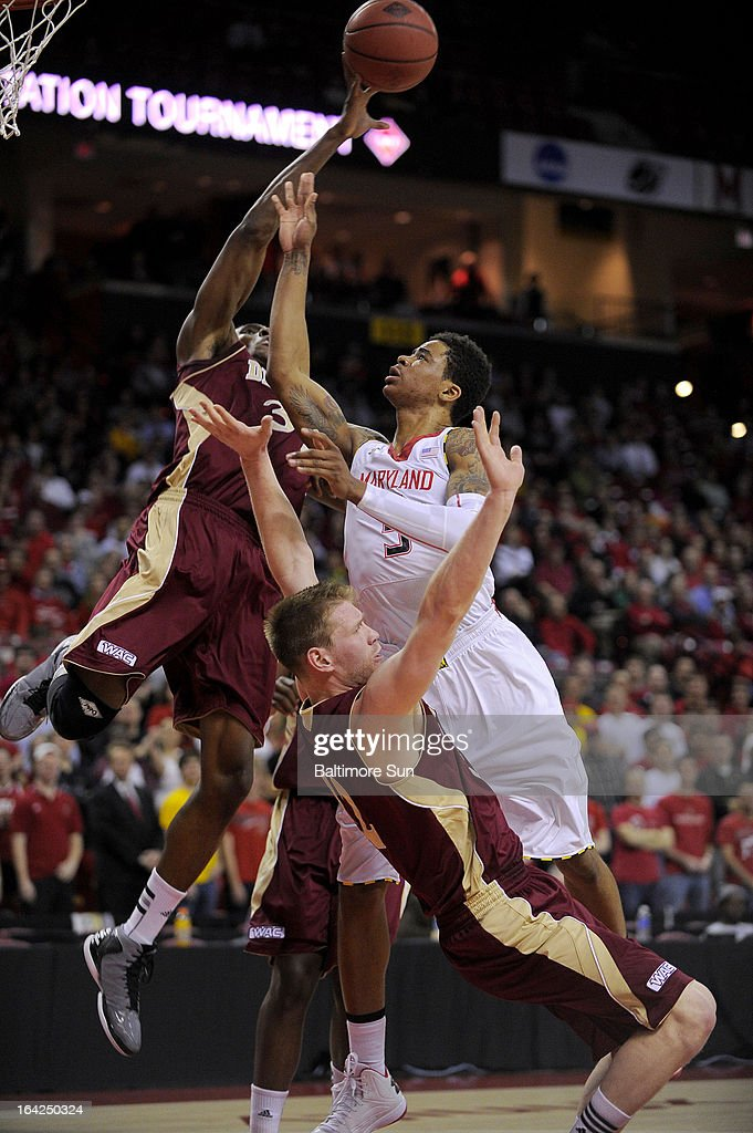 Maryland's Nick Faust cannot get his shot past Denver defenders Chris Udofia (34) and Chase Hallam (32) during first-half action in the NIT basketball tournament at the Comcast Center in College Park, Maryland.