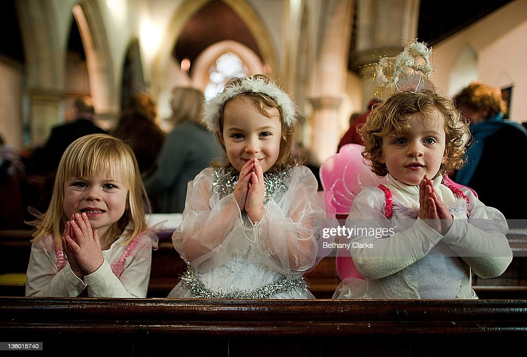 Mary-Sarah Dean, Emily Walsh and Emily Frew, angels, wait for their cue during a traditional Christmas Nativity on December 18, 2011, at St Mary's Church, Myton Village, England. In schools and churches around the country children busy preparing and performing in the telling of the traditional nativity story.