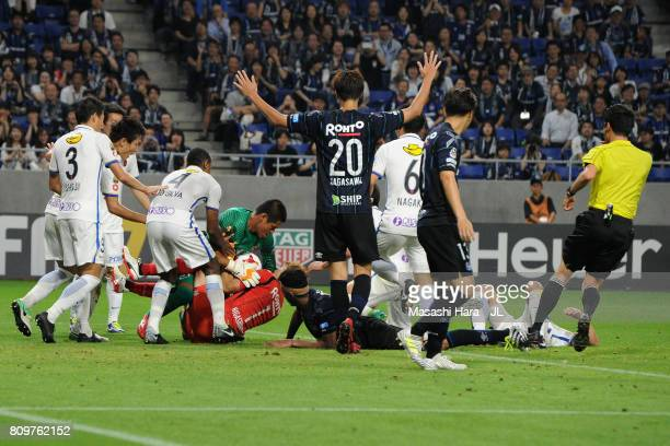 Masaaki Higashiguchi of Gamba Osaka and Hitoshi Sogahata of Kashima Antlers battle for the ball during the JLeague J1 match between Gamba Osaka and...