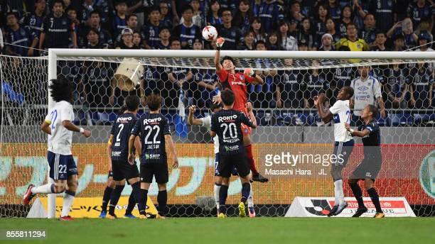 Masaaki Higashiguchi of Gamba Osaka and Hugo Vieira of Yokohama FMarinos compete for the ball during the JLeague J1 match between Gamba Osaka and...