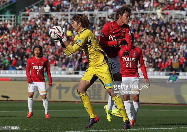Masaaki Higashiguchi of Gamba Osaka and Tadanari Lee of Urawa Red Diamonds compete for the ball during the FUJI XEROX SUPER CUP 2015 match between...